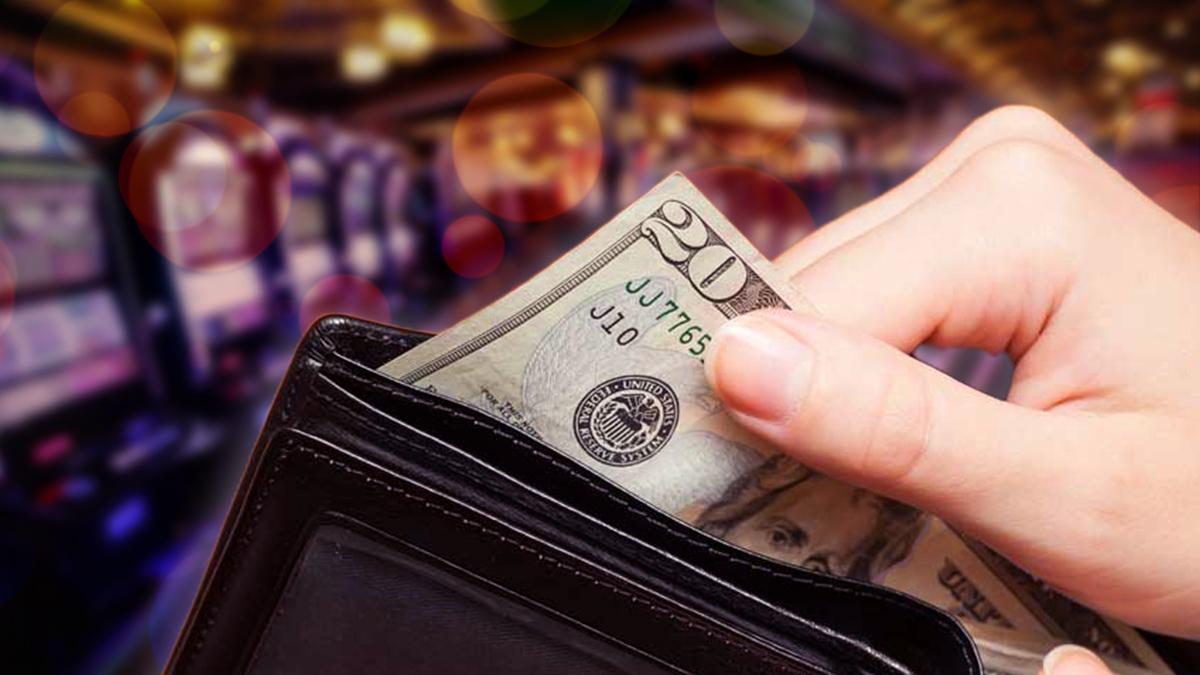 Tangan Menghapus Uang 20 Dolar Dari Dompet Dengan Latar Belakang Kasino